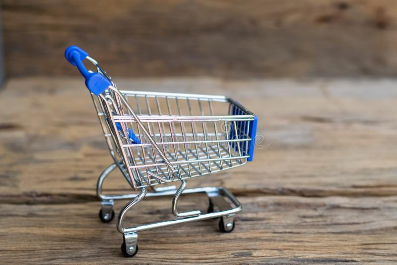Mini Shopping Cart. Shopping cart on an old wood background. Sale concept royalty free stock image