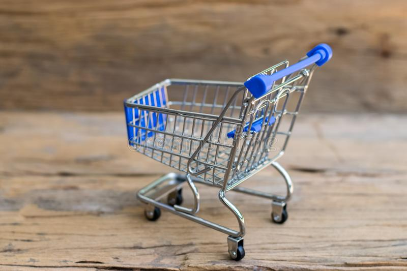 Mini Shopping Cart. Shopping cart on an old wood background. Sale concept royalty free stock photos