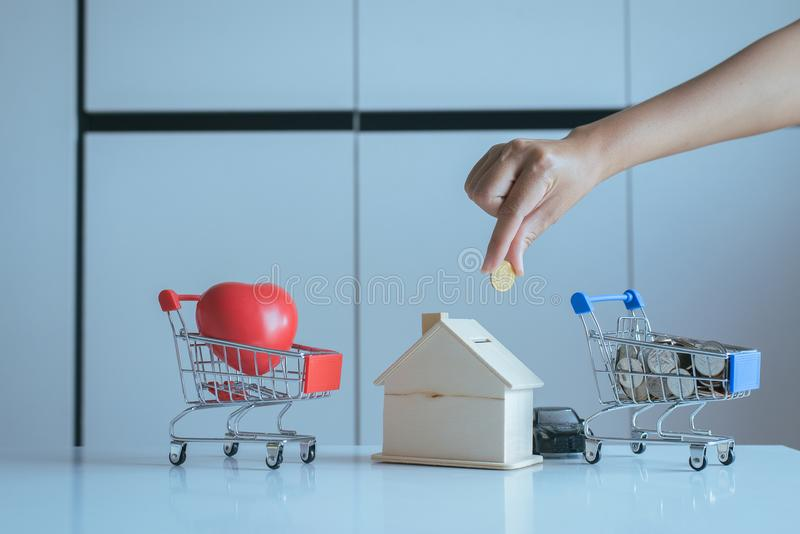 Mini shopping cart,Red heart model,Coins stack with hand putting of coins on piggy bank,Finance and money saving concept royalty free stock photography