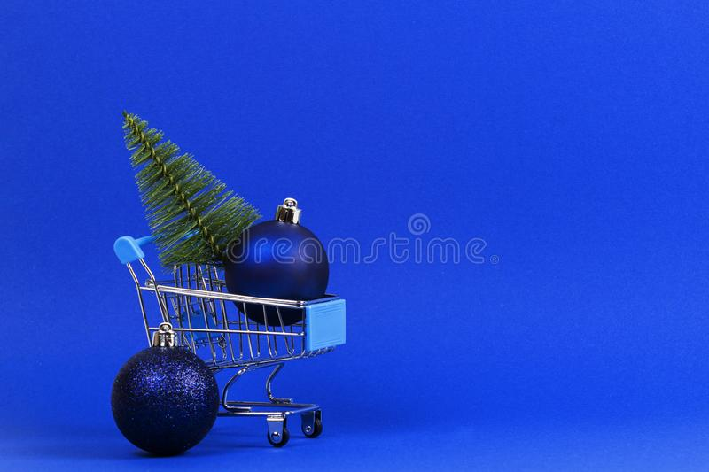 Mini shopping cart with small Christmas tree and navy Christmas decoration bauble balls on blue background.  royalty free stock photography