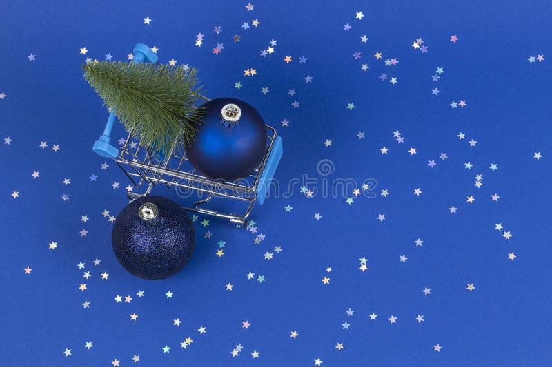 Mini shopping cart with small Christmas tree and navy Christmas decoration bauble balls on blue background with silver. Mini shopping cart with small Christmas royalty free stock photos