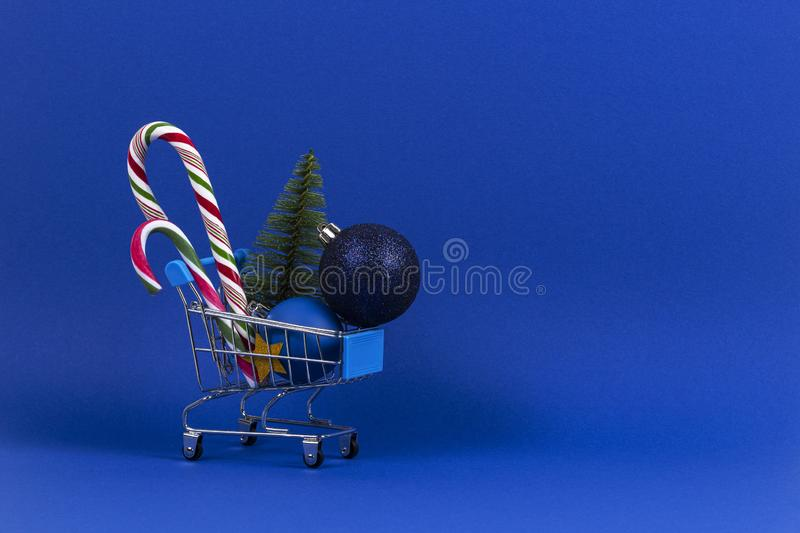 Mini shopping cart with small Christmas tree, Xmas decoration bauble balls and candy canes on navy blue background.  royalty free stock photography