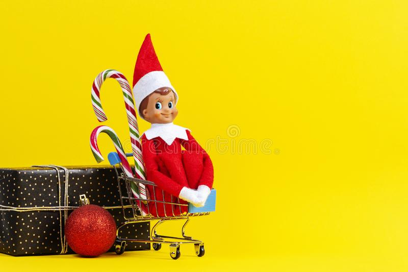 Mini shopping cart with small toy Santa elf and candy canes, Xmas decoration bauble ball and present gift box on yellow stock images