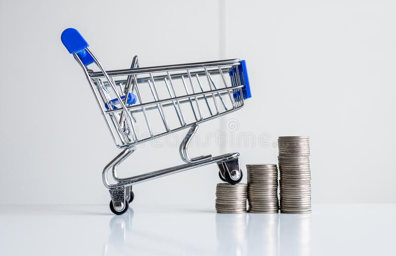 Mini shopping cart with step of coins stacks,Finance and money shopping concept royalty free stock images
