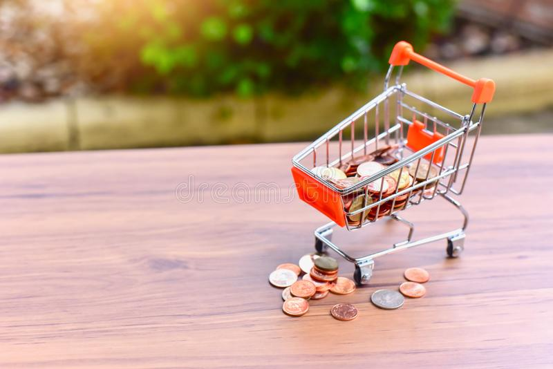 Mini Shopping Cart or Trolley and Glass Jar Filled with Coins Isolated on a Table as for Retail Business. Mini Shopping Cart For Retail Business Filled with stock photography