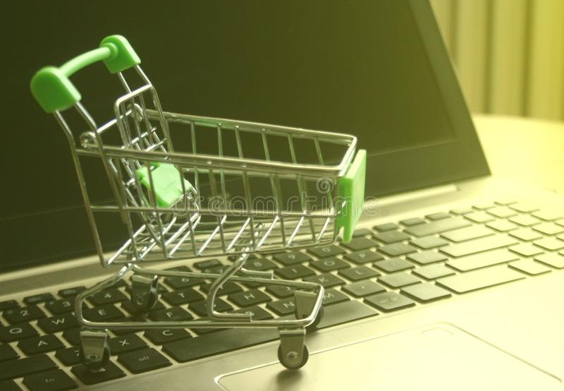 Mini shopping trolley on laptop keyboard that shines on the sun symbolizing marketing and shopping as a concept of business stock photos