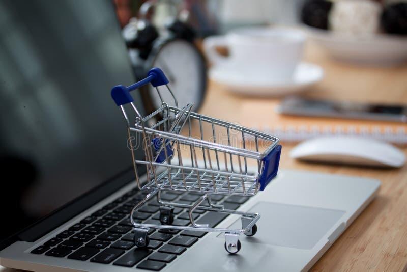 Mini- shoppingvagn på datorbärbara datorn äganderätt för home tangent för affärsidé som guld- ner skyen till royaltyfria bilder