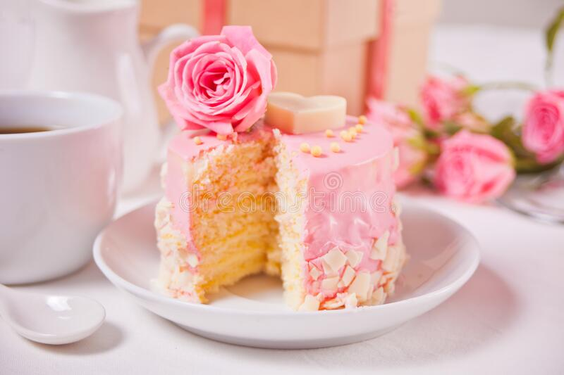 Mini small cake with pink glaze, beautiful roses, cup of coffee, gift box on the white table. Mini cake with pink glaze, beautiful roses, cup of coffee, gift box stock image