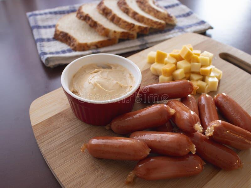Mini Smoked Sausages Cocktail Wieners com mistura picante do mergulho de cubos do queijo e de fatias do p?o da batata fotografia de stock royalty free