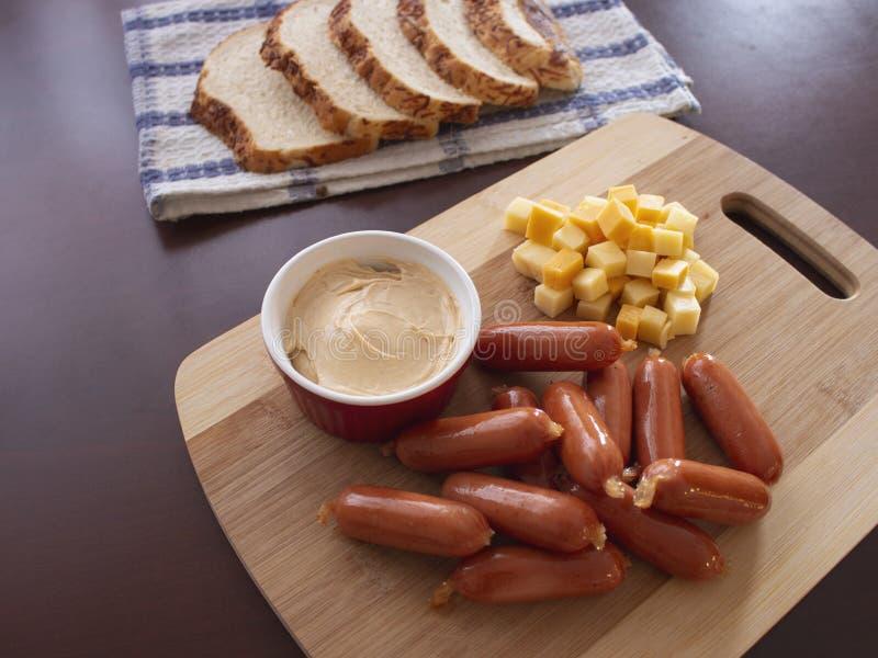 Mini Smoked Sausages Cocktail Wieners com mistura picante do mergulho de cubos do queijo e de fatias do p?o da batata imagens de stock royalty free