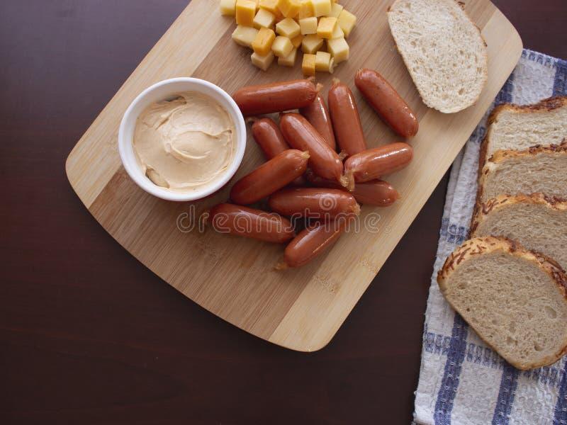 Mini Smoked Sausages Cocktail Wieners com mistura picante do mergulho de cubos do queijo e de fatias do p?o da batata fotografia de stock