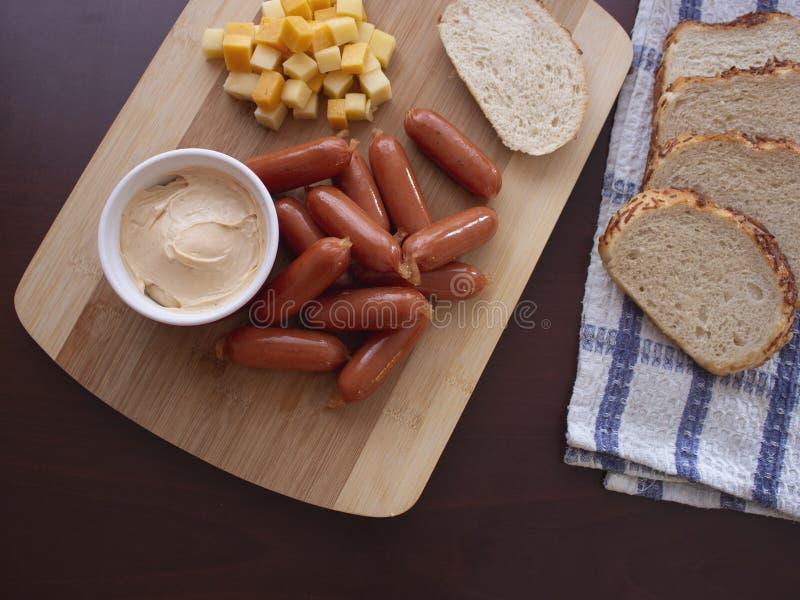 Mini Smoked Sausages Cocktail Wieners com mistura picante do mergulho de cubos do queijo e de fatias do p?o da batata foto de stock