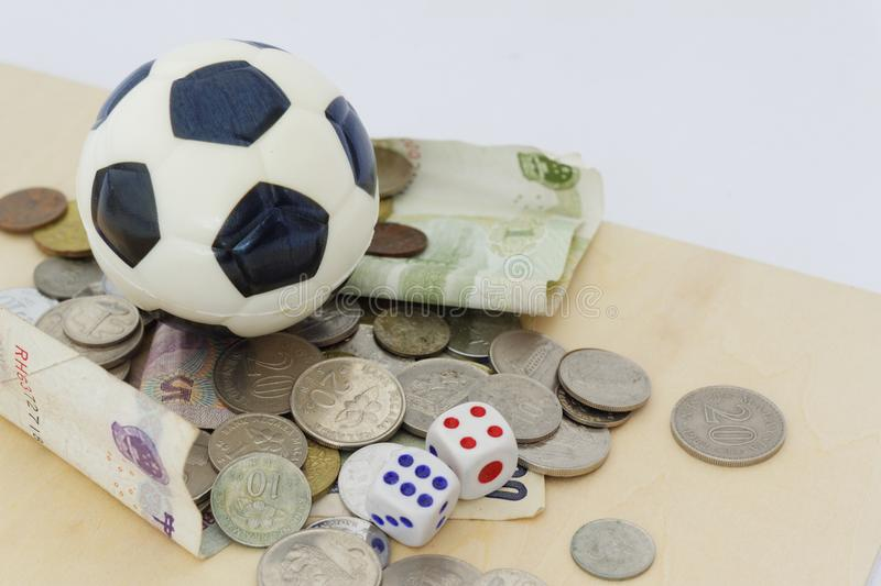 Mini soccer ball on top of playing cards with dices and money in different currency. royalty free stock images