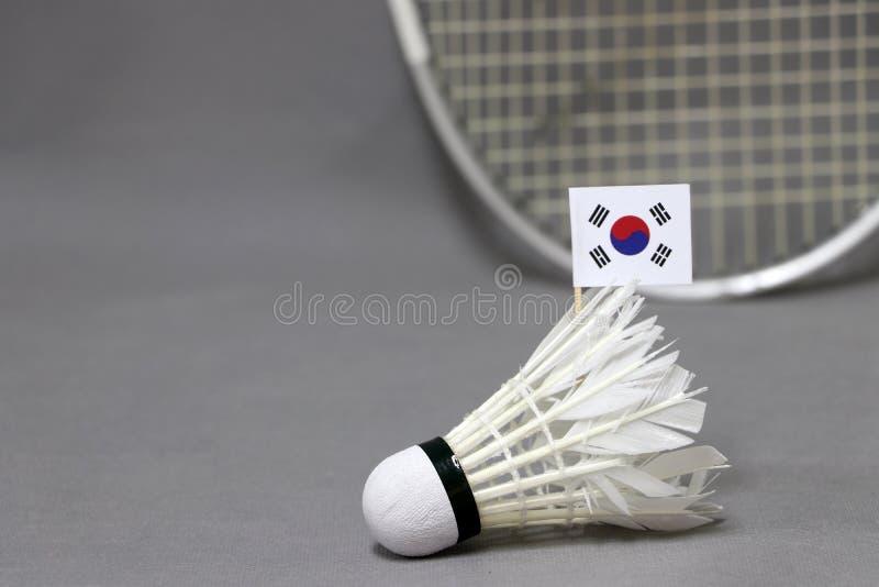 Mini South Korea-Flaggenstock auf dem weißen Federball auf dem grauen Hintergrund und fokussieren heraus Federballschläger stockfotografie