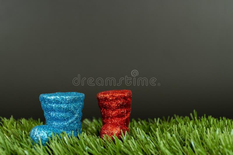 Mini stivali della decorazione variopinta di natale di plastica sul prato inglese con un fondo grigio scuro immagini stock libere da diritti
