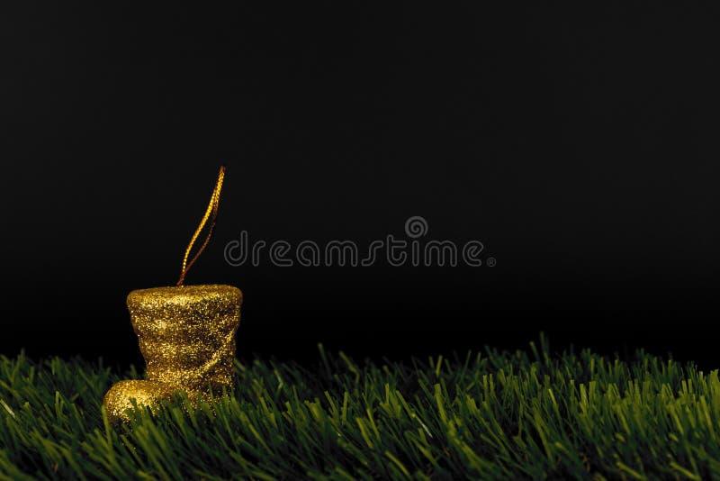 Mini stivali della decorazione variopinta di natale di plastica sul prato inglese con un fondo nero fotografia stock libera da diritti