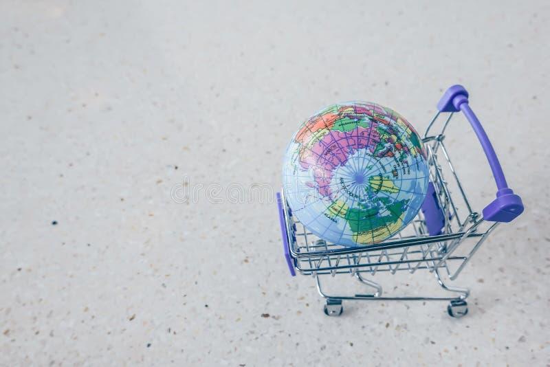 Mini supermarché de caddie/chariot avec la carte de ballon de globe du monde, les achats en ligne et le concept de commercialisat image stock