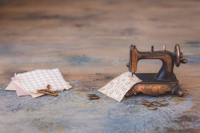 Mini- symaskin för tappning med sax, knappar och tyg på lantlig bakgrund arkivfoton