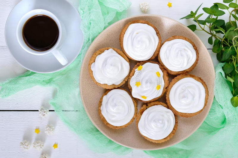 Mini tart with an air cream on a plate and a cup of coffee on a white wooden background. royalty free stock photos