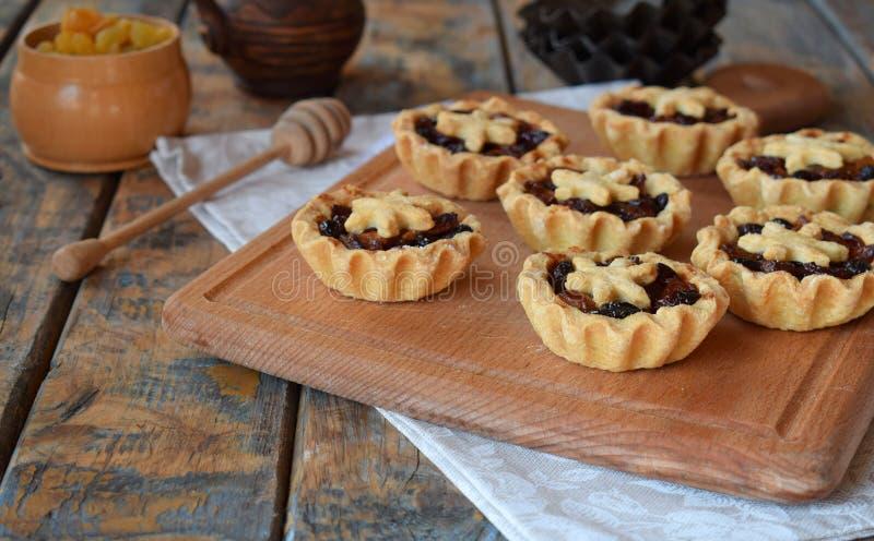 Mini Tartlets mit Trockenfrüchten und Nüssen Keksplätzchen mit den Früchten, die auf hölzernem Hintergrund anfüllen Kleine süße T stockfotos