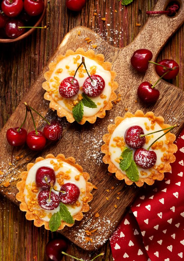 Mini Tarts with fresh cherries and vanilla custard and caramel, delicious dessert on a wooden table royalty free stock photo