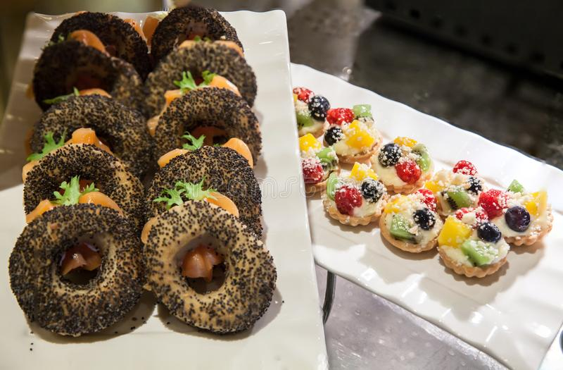 Mini- tarts med kräm och bär Läckra mini- tarts med ny bär och vaniljsås på tabellen royaltyfria bilder
