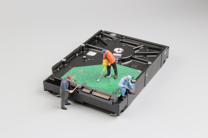 Mini techniciens étroitement une unité de disque dur pour des virus, image libre de droits