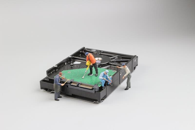 Mini- tekniker nära en hårddisk för virus, fotografering för bildbyråer