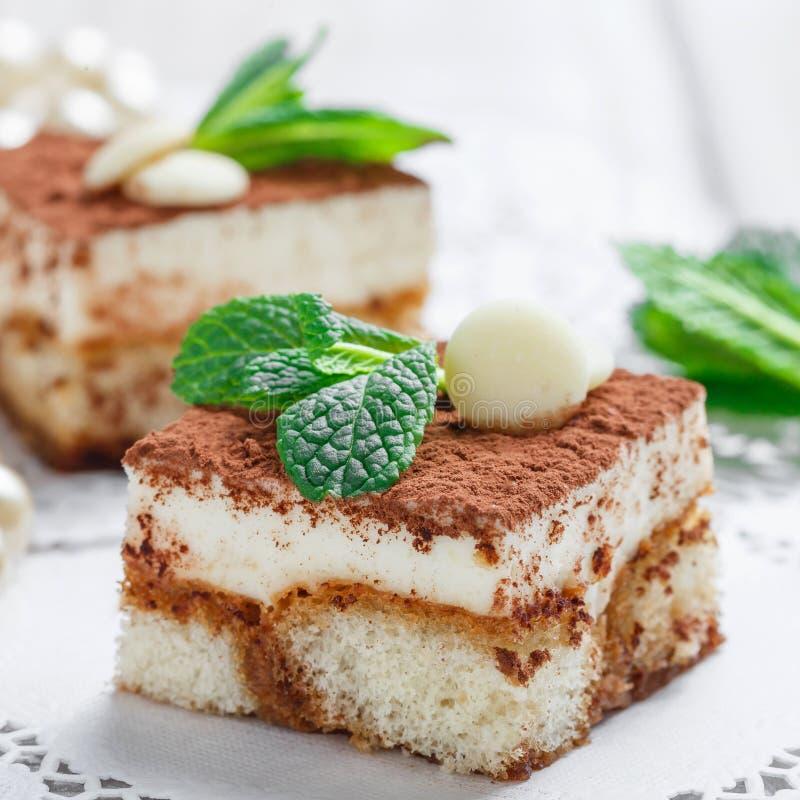 Mini tiramisù dei dolci con cioccolata bianca, cacao e le caramelle sulla fine leggera del fondo su immagine stock