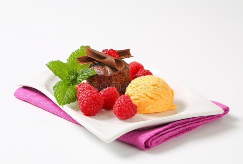Mini torta de chocolate con las frambuesas y el helado frescos imagenes de archivo