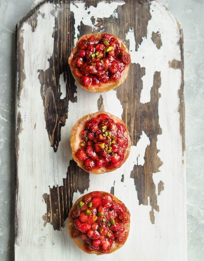 Mini-torta di formaggio casalinga tre con le fragole di bosco immagine stock