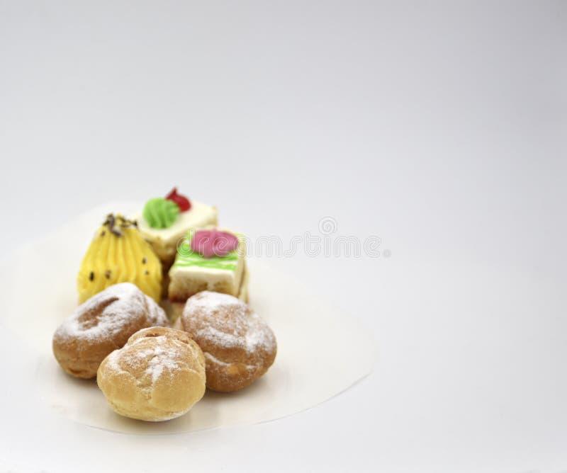 Mini tortas y soplos aislados con el polvo de la crema y del azúcar imagen de archivo