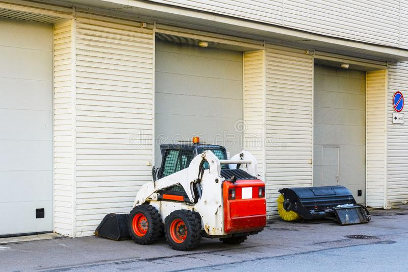Mini tractor with a blade and a bucket for street cleaning is at the gate of a large garage. A small mini tractor with a blade and a bucket for street cleaning royalty free stock photos