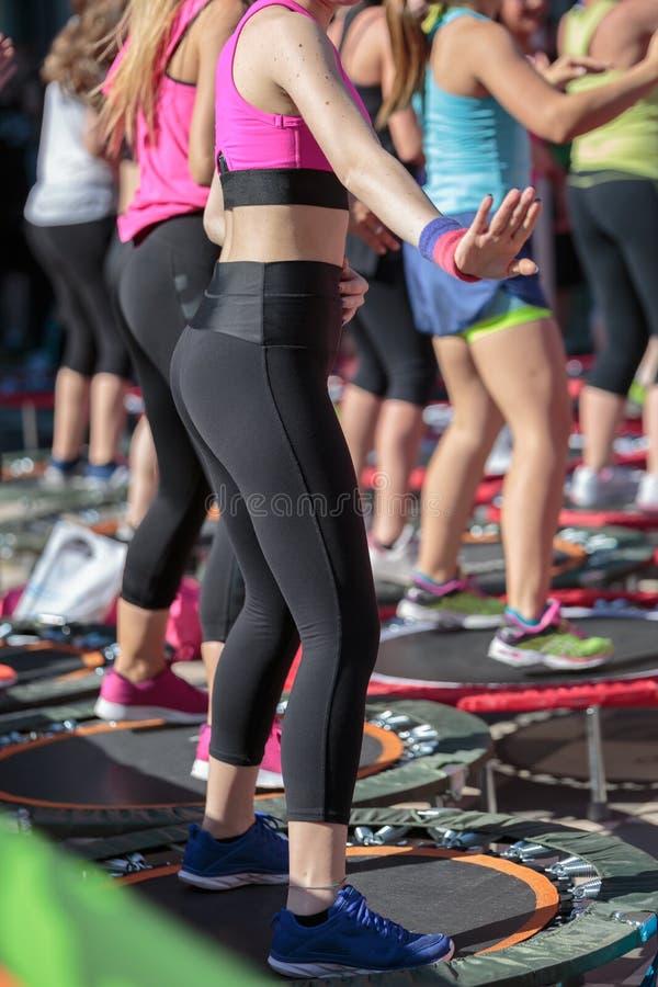 Mini Trampoline Workout: Die Mädchen, die Eignung tun, trainieren Klasse in der im Freien an der Turnhalle lizenzfreies stockbild