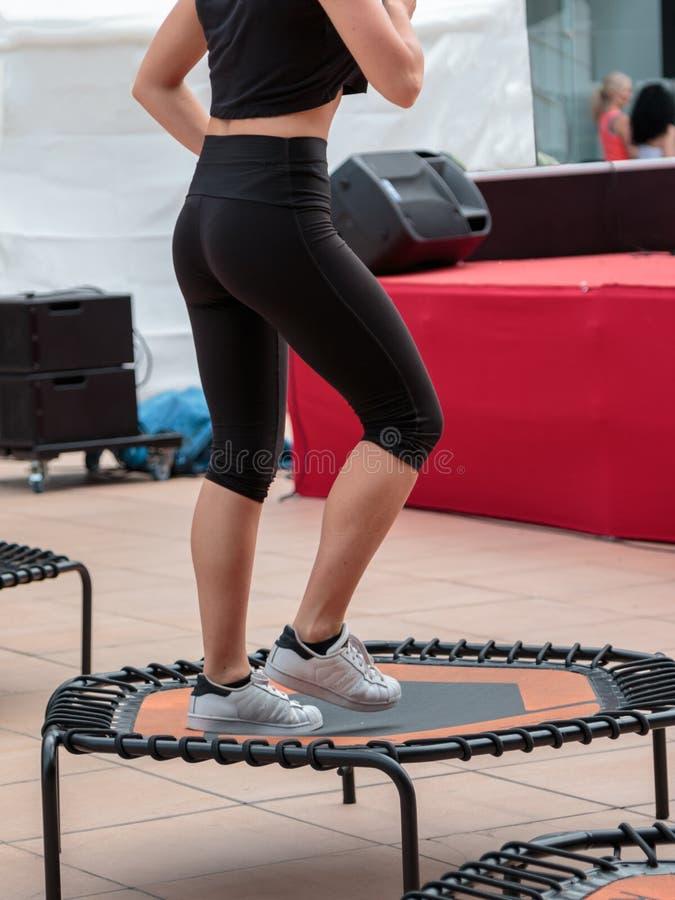 Mini Trampoline Workout: Mädchen, das Eignungs-Übung in der Klasse an der Turnhalle tut stockfotografie