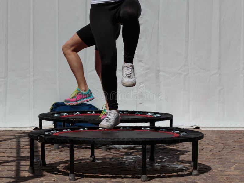 Mini Trampoline Workout: Mädchen, das Eignungs-Übung in der Klasse an tut stockfoto