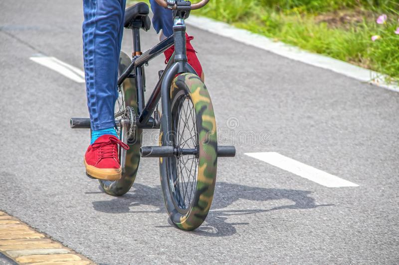 Mini trick stunt bike with camouflage fat tires and pegs being ridden by guy in red tennis shoes and blue jeans on paved surface stock images