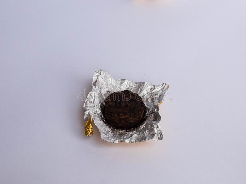 Mini tuocha pressed Pu`er tea from Chinese province Yunnan wrapped in golden foil on white background royalty free stock image