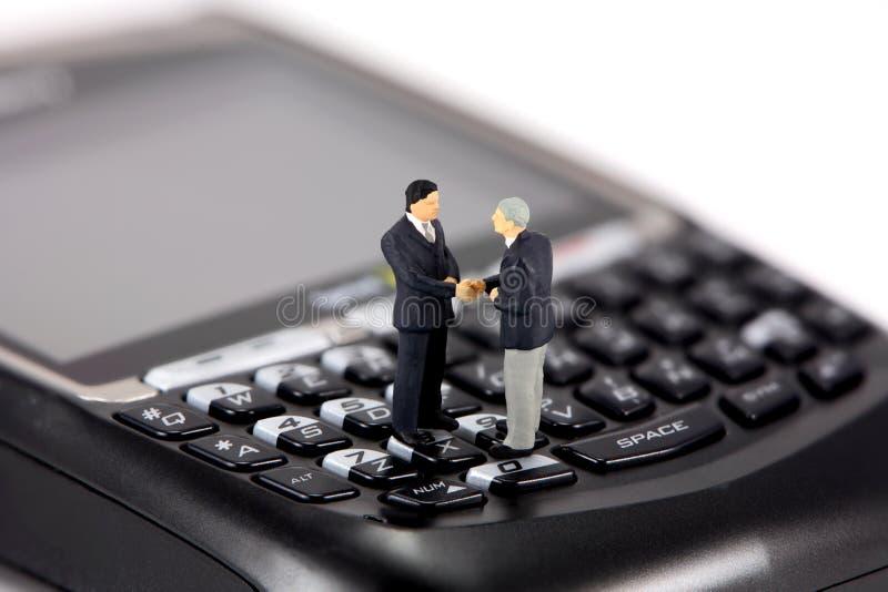 Mini uomini d'affari sul cellulare fotografia stock