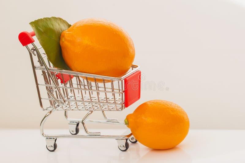 Mini- vagn, organiska ljusa citroner för spårvagnshoppinghäxa på ljus bakgrund Begrepp av sund matshopping, detox royaltyfri foto