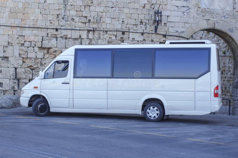 Mini Van bus blanc s'est garé sur les passagers de attente de rue photos libres de droits