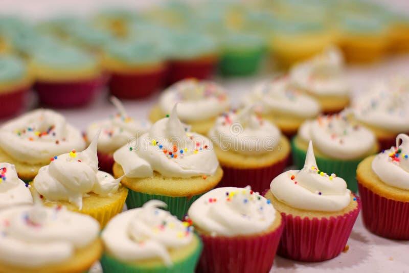 Mini- vaniljmuffin som glaseras och dekoreras för ett barns födelsedagparti arkivfoton