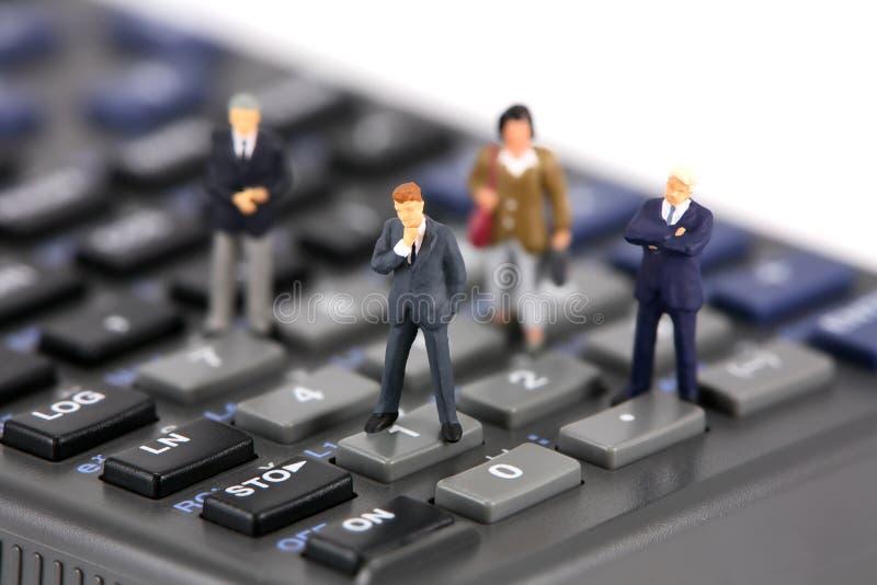 Mini zakenlieden op calculator royalty-vrije stock afbeelding