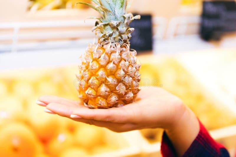 Miniananas in der weiblichen Hand im Supermarkt lizenzfreie stockfotos
