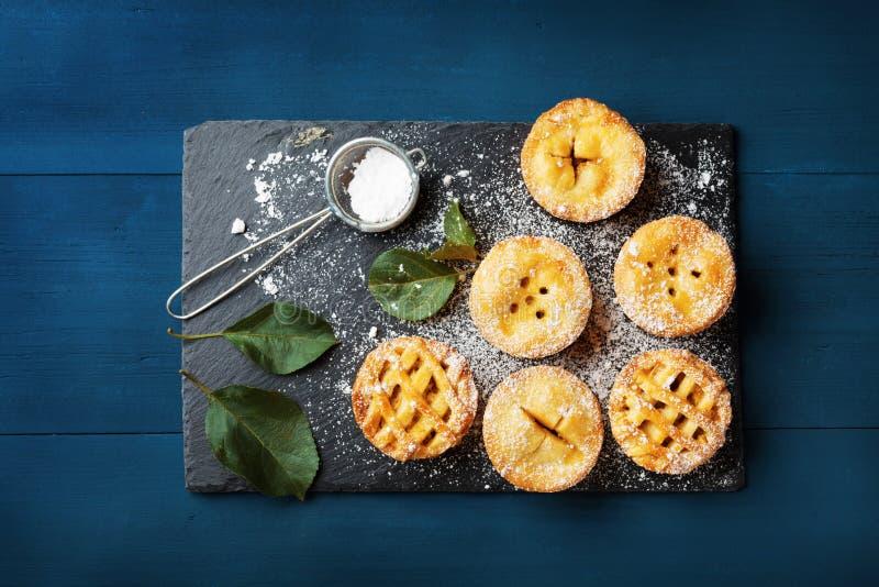 Miniappeltaarten verfraaid suikerpoeder op blauwe lijst van hierboven Het heerlijke dessert van het de herfstgebakje royalty-vrije stock afbeelding