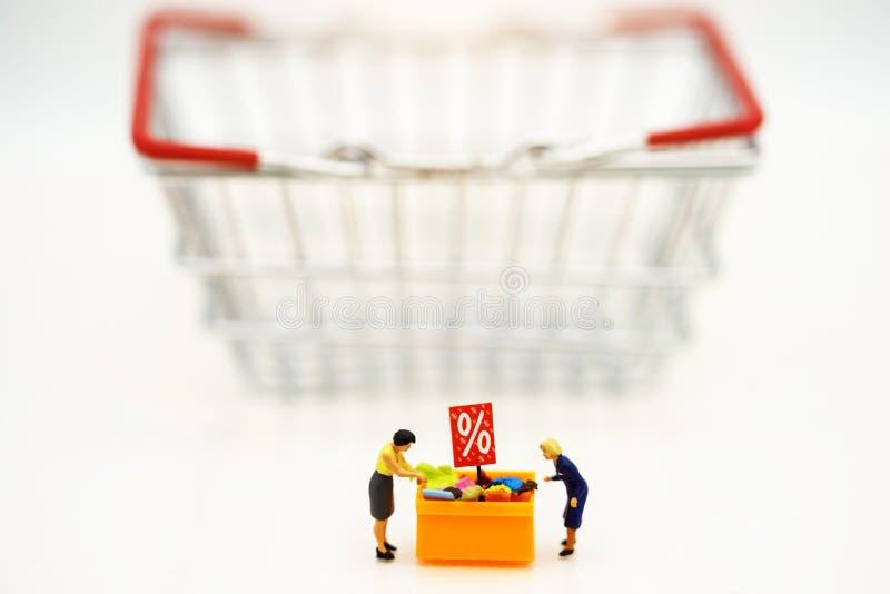 Miniatruemensen: De klanten kopen goederen op verkoop met kortingsdienblad en boodschappenwagentje royalty-vrije stock foto's