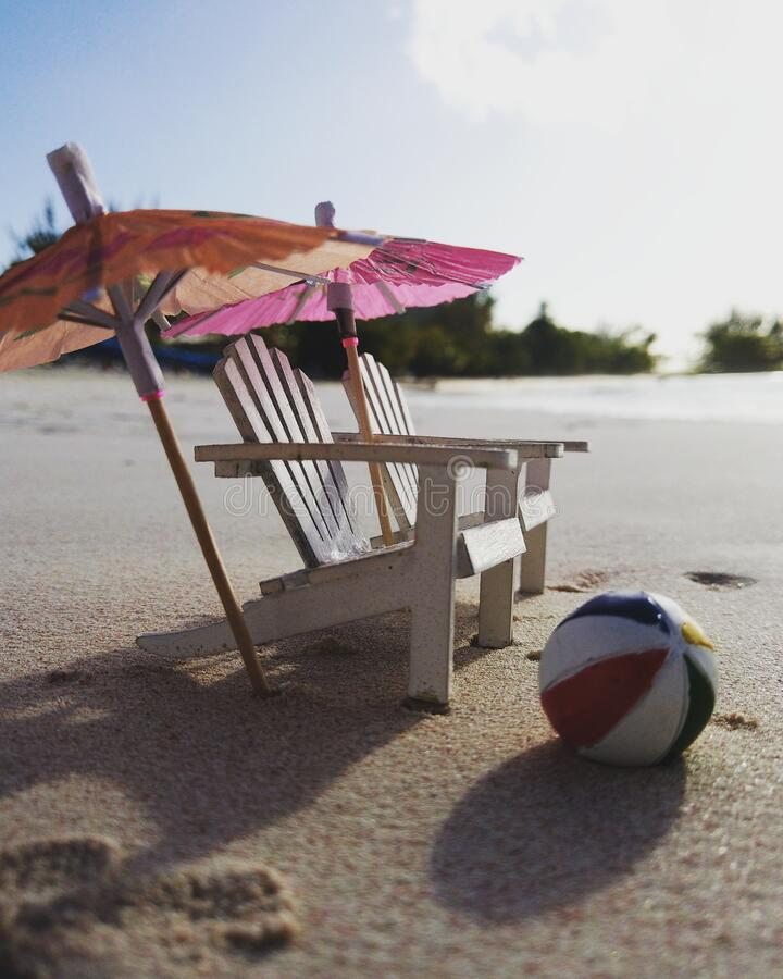 Miniatur-Adirondack-Stühle, Sonnenschirme und ein Beachball stockfotos