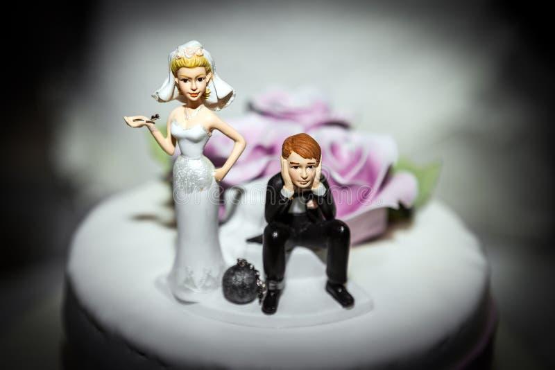 Miniatur der Braut und des Bräutigams auf Hochzeitstorte stockfoto