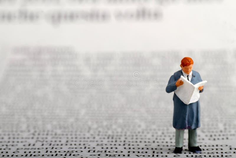 Miniatur eines Geschäftsmannes, der eine Zeitung liest lizenzfreie stockbilder