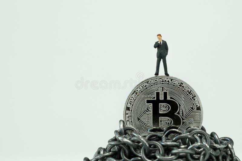 Miniatur- Geschäftsmann, der auf Bitcoin auf Ketten-mounta steht stockfoto
